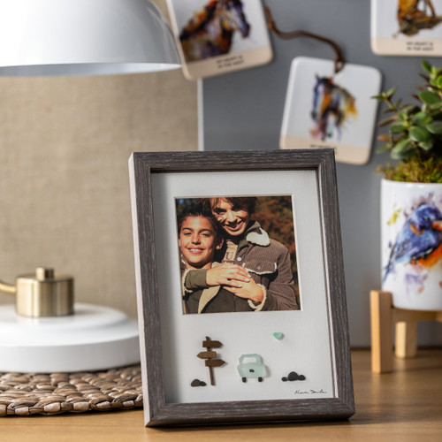 A close up image of a wooden desk topped with a pebble art piece picture frame, enclosing a family photograph and a pebble art scene of a car on a road. Pictured in front of a lamp, a planter, and a magnet set.
