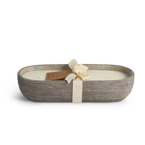 A large, oval, black washed, concrete candle. Wrapped in an ivory bow, with a brown cardboard hangtag.