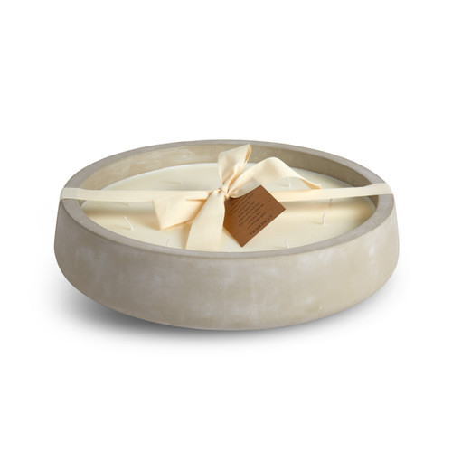 A large, circular, white washed, concrete candle. Wrapped in an ivory bow, with a brown cardboard hangtag.