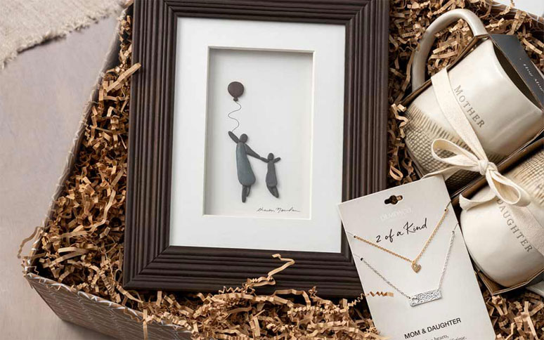 Gift box of mother gifts. Mother Daughter mugs, 2-of-a-kind Mom and daughter necklaces, and framed pebble art of a mom and daughter.