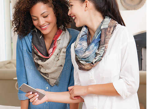 Two young women looking at a mobile phone smiling together