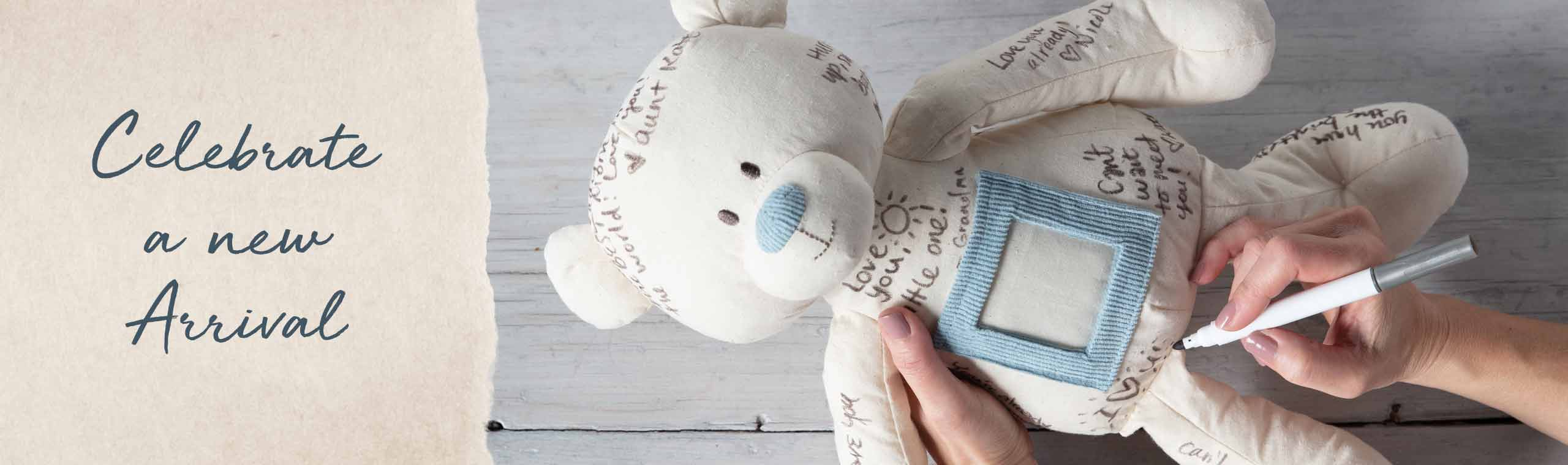 Celebrate a New Arrival. Someone writing a loving message on a white stuffed bear.