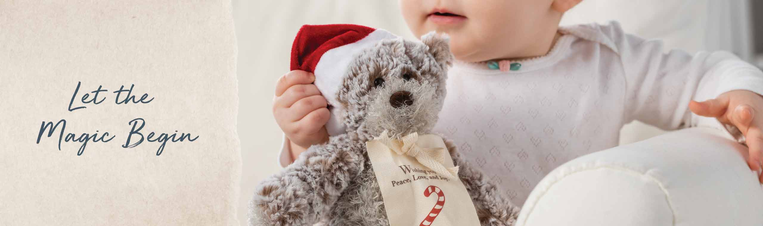 Let the magic begin. Baby hugging a small teddy bear wearing a santa hat.