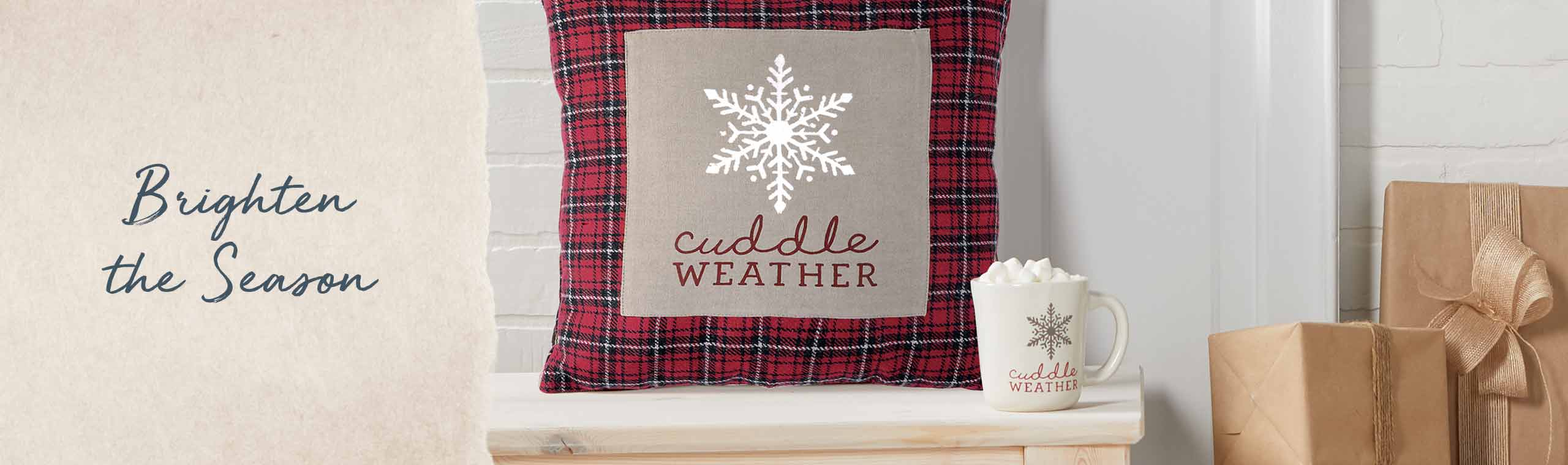 Brighten the season. Pillow and mug setting on a wooden bench, both decorated in the words Cuddle Weather.
