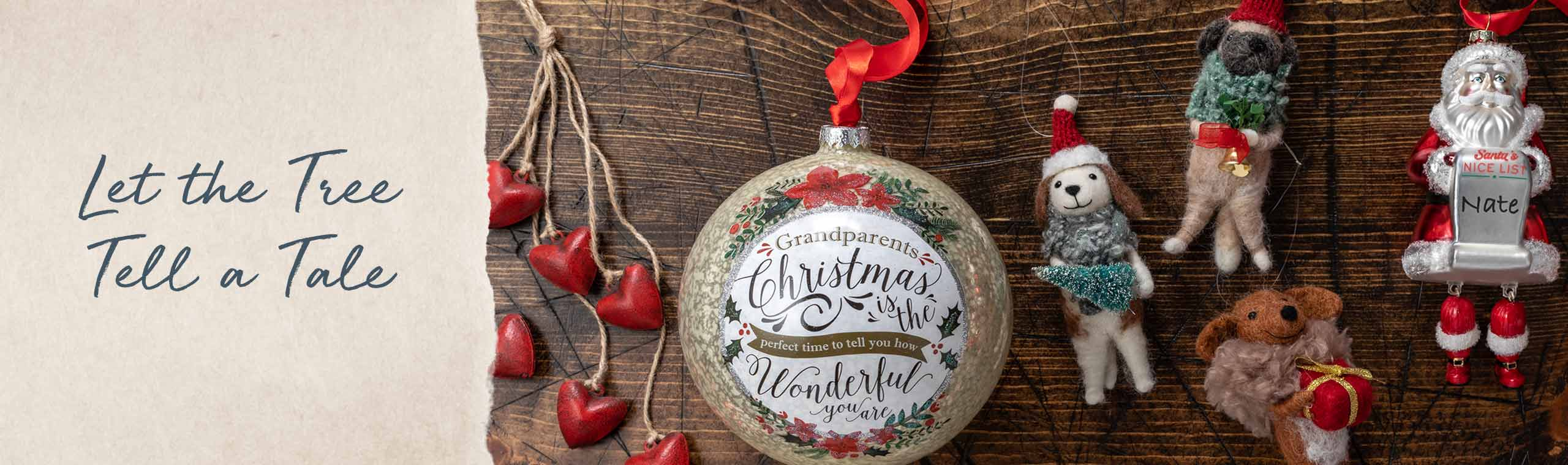 Let the tree tell a tale. Christmas ornaments lying on a wood table. Red hearts on strings. Large bulb with the words Grandparents Christmas is the perfect time to tell you how wonderful you are. Fuzzy dogs holding bells and a christmas tree.