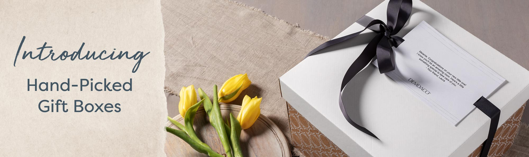 Introducing Hand-Picked Gift Boxes. White and gold box tied with a dark ribbon, next to yellow flowers.
