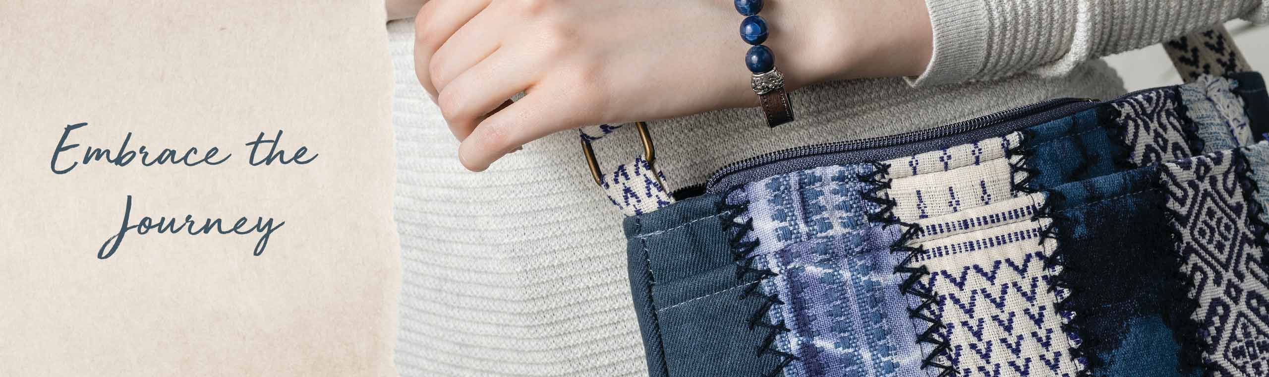 Embrace the Journey. Closeup of woman carrying a blue hand-stitched bag and wearing a blue beaded bracelet