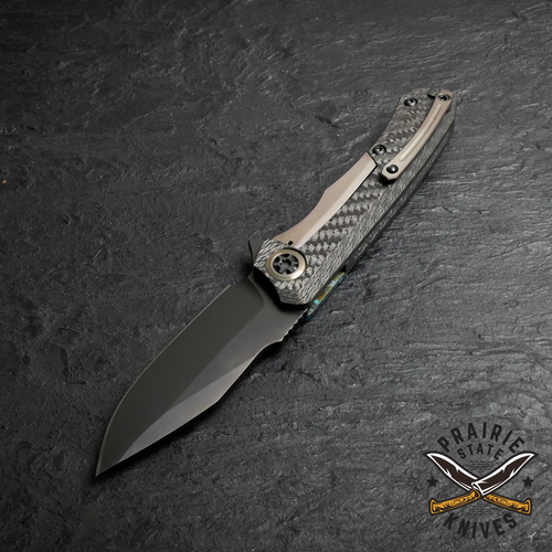 single piece carbon fiber handle with a bronze titanium pocket clip, pivot collar, and lock bar.