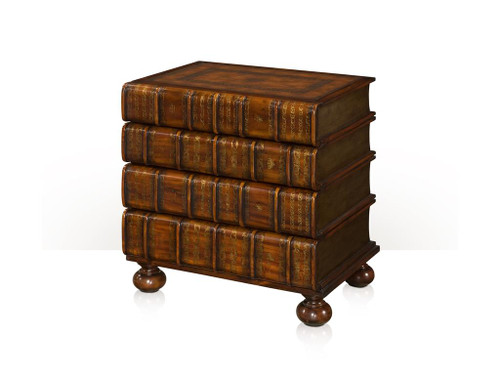 A hand carved and gilt faux book chest of drawers