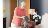 Old man putting the Philips Respironics DreamStation Go Auto CPAP in a bag