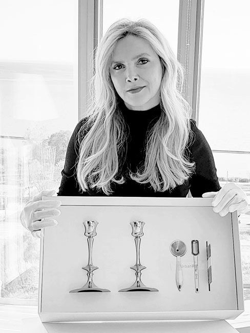 Agnes Galas showing the packaging box and 2 candlesticks with funnel and spoon.