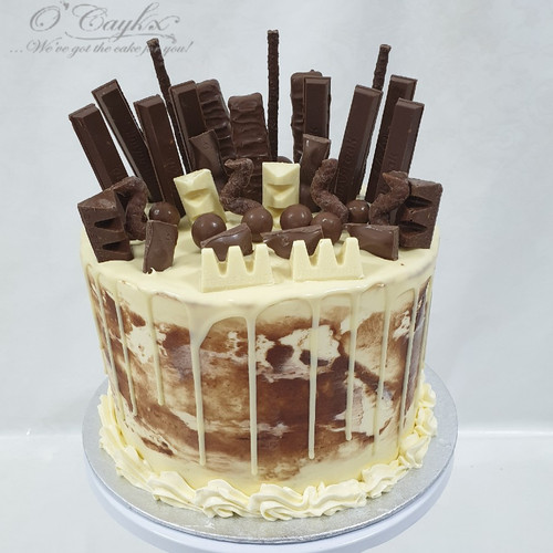 White Chocolate Sweetie Drip cake  Please note that types of chocolates/sweeties used, are subject to availability, and therefore might not look exactly like image represented