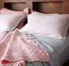 Styling image with the Musk pink Coverlet as a blanket, and showing the Vintage Linen bed sheets as a combination set.