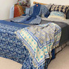 Styled bed with indigo blue, kantha kimono, throw blanket, quilt and coverlet.