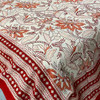 Lotus design floral tablecloth, featuring burnt reds and rusty tones on a white background that creates drama in the design.