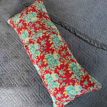 Vintage Kantha hand-stitched cloth made into a lumbar support pillow cover 30 x 70 cms. Showing that it is the length of a standard bed pillow.