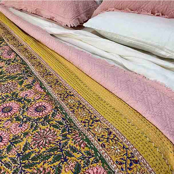 Dusty pink daisy flowers float on a mustard background on this kantha stitched quilt.