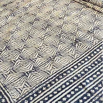 Hand block printed Kantha quilt in charcoal blue with paper lantern style print on a white background.