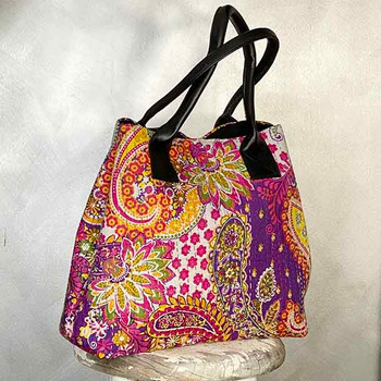 Purple paisley design tote shopping bag, with two black handles.