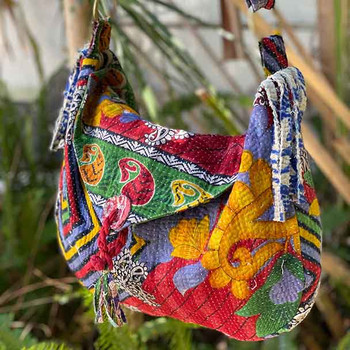 Showing bright red, orange, green with large flowers and geometric shapes. Cut tassles hang from the sides giving a boho vibe.