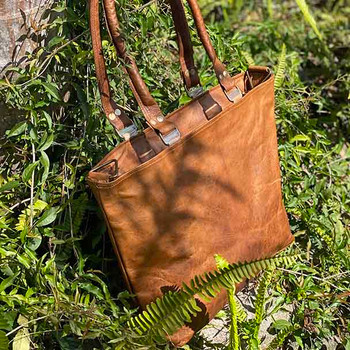 Showing a tan coloured leather tote bag, with two sturdy leather straps.