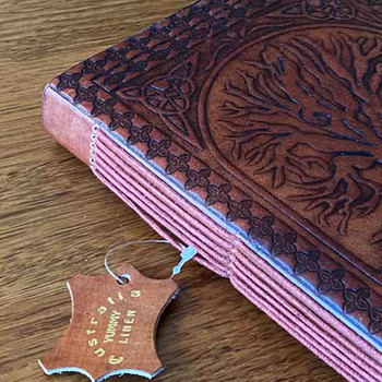 Detail image that shows the lovely binding of the pages in the book, as well as the tan coloured leather cover.