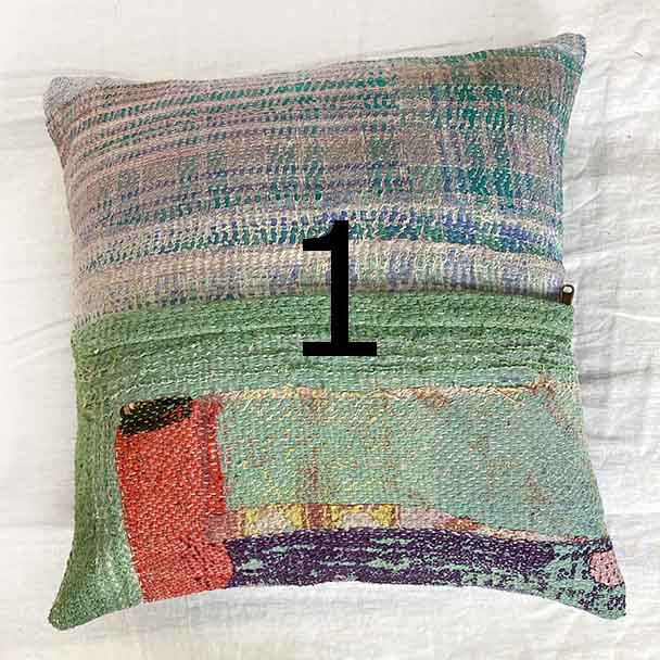 Rugged vintage cloth cushion cover in an abstract design of coastal greens, vibrant orange and checkered pinks and purples.