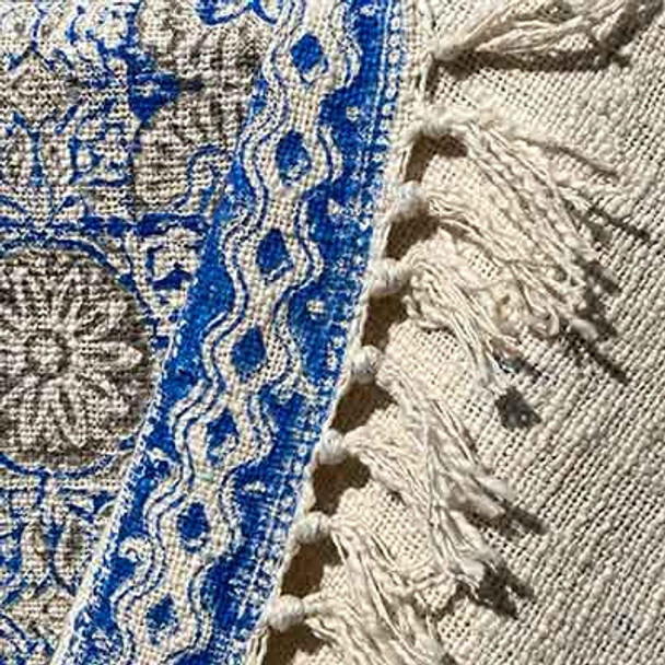 The pattern is in shades of blue and has fringing on either end.