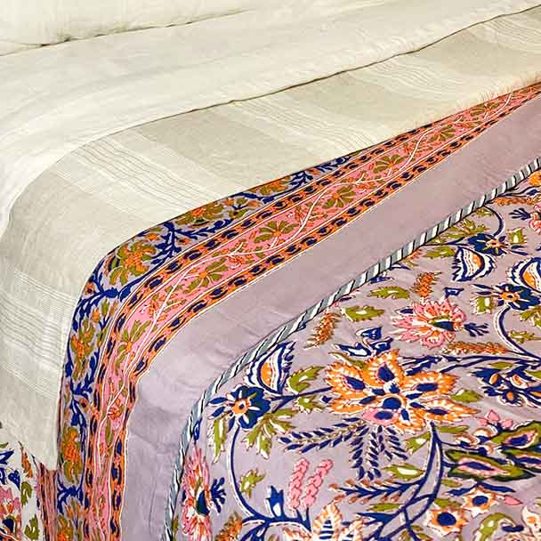 Dusty Lilac super soft quilted cotton floral bed sheet in shades of dusty lilac, orange, green and pink shown with pure linen sheets.