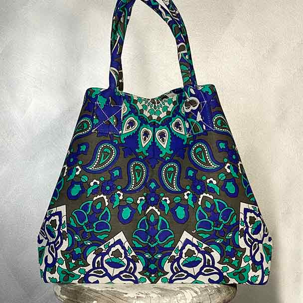 Blue and green mandala print tote shopping bag with a circular design. Folded into the smaller triangular shape.