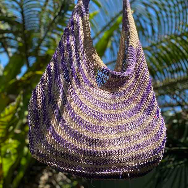 Natural fibre and dyed Bilum bag with a striped purple and natural pattern.