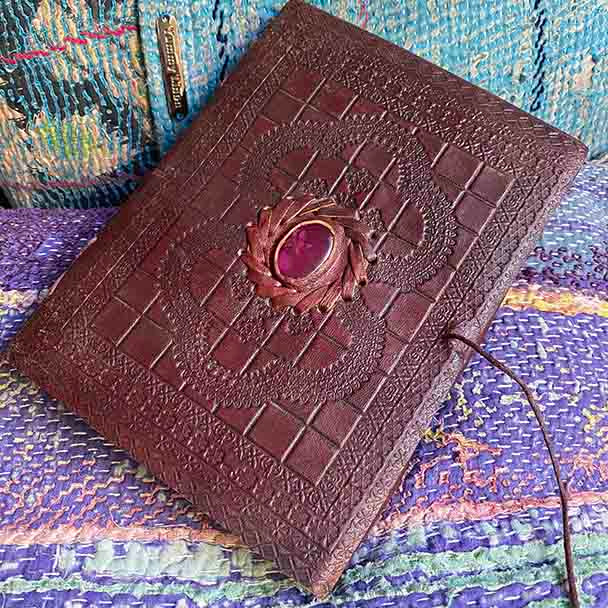 Embossed leather covered journal with a ruby coloured stone central to the design. 6 x 8 inches.