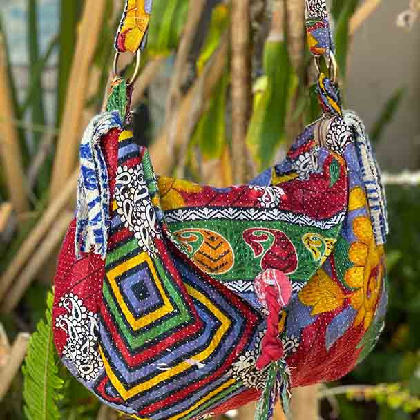 Very bright red, orange, green with large flowers and geometric shapes. Cut tassles hang from the sides giving a boho vibe.