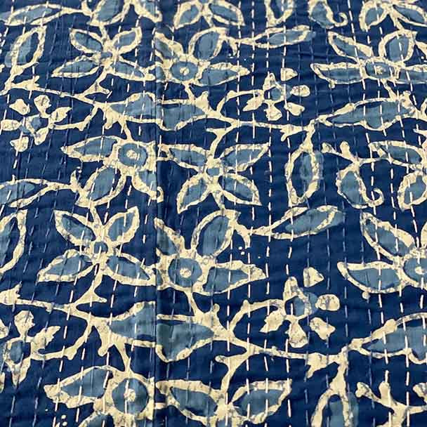 Indigo blue hand stitched Kantha quilt showing the two tones of blue flowers outlined in white.