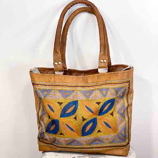 Showing the embroidered design sitting on a tan coloured tote bag, with two sturdy leather straps.
