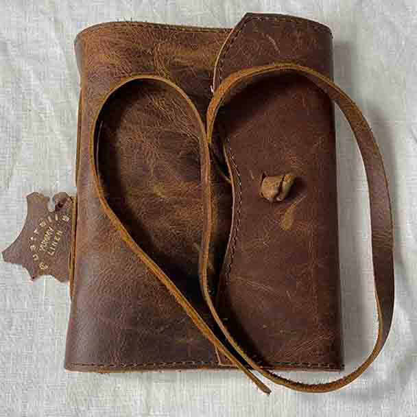 showing the strap closure of the vintage style soft covered leather note book.