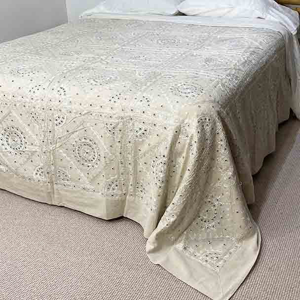 Raw white cotton bedspread with beautiful hand stitched silk design and small mirror centers.
