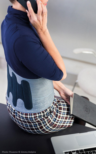 LombaSkin® - Second Skin effect compact lumbar support belt on woman sitting.
