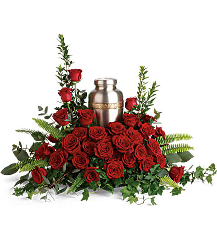 Elegant red roses and delicate greenery are a breathtaking way to display and honor the cremation urn.