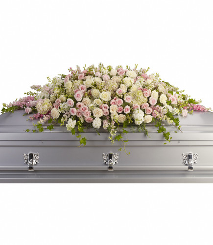 A beautiful casket spray of soft pink, white and crème blooms ease the burden of loss.