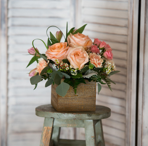 Wooden box filled with peach and pink flowers