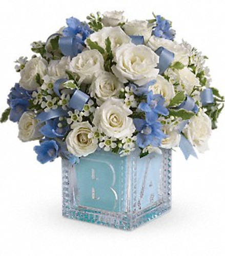 White and blue flowers in a keepsake glass baby block