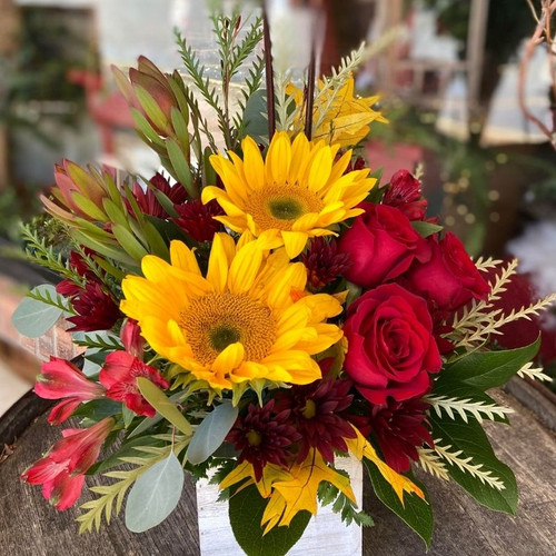 Bright Sunflowers, red roses and more in a rustic farmhouse box.
