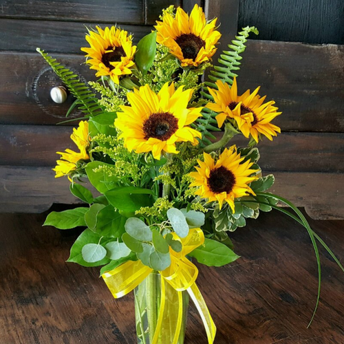 A modern twist on sunflowers with looped bear grass in a tall glass vase.