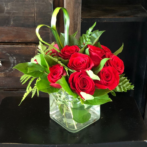 Our Love Squared Roses bouquet features 12 red roses and bear grass hand-tied in a modern style cube.