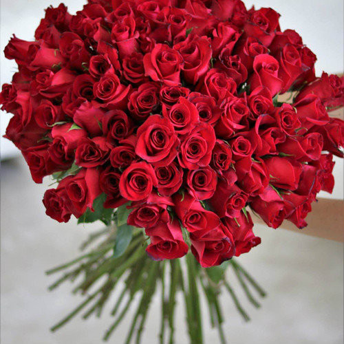 100 of our finest roses artfully designed in a large glass vase.