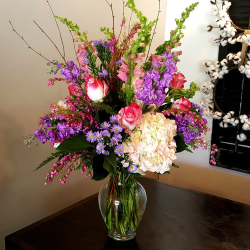 Variegated pink roses, white hydrangea, purple stock, belles of Ireland, snapdragons, dahlias & pink dingle berry flowers.
