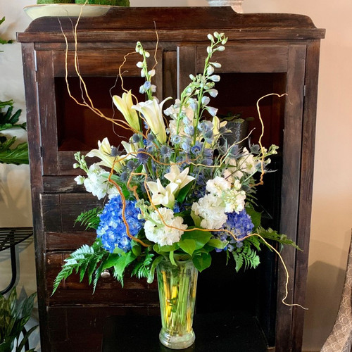 Send the Blue For You Floral arrangement featuring blue hydrangea, blue delphinium, thistle, white stock blooms, white lilies, fern accents and branches.