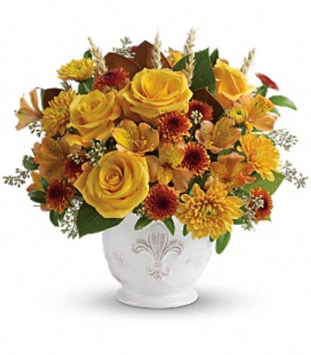 Golden and fall colored flowers in an  French Country pot.