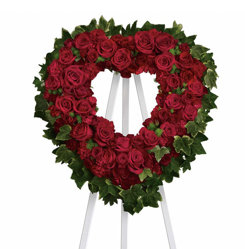 Red roses and carnations make up this beautiful heart shaped stand.